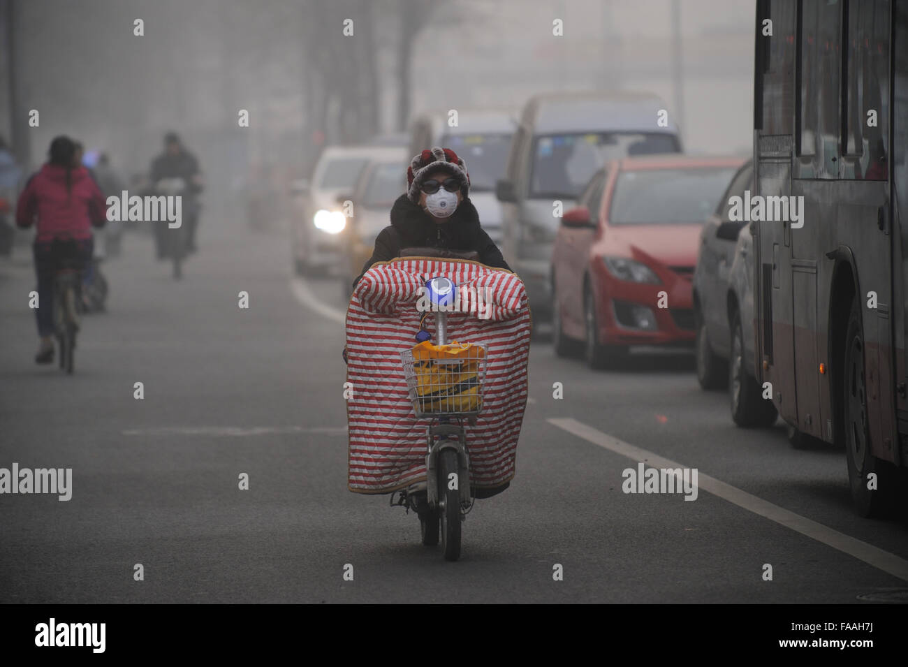 People wear masks as a thick haze of air pollution envelopes Beijing, China. 25-Dec-2015 - Stock Image