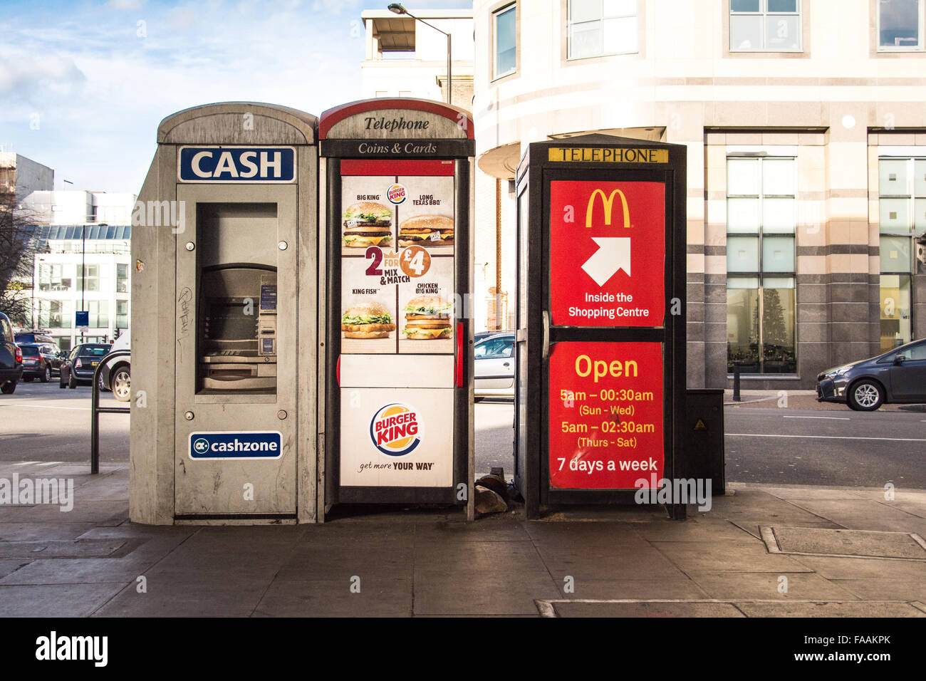 Neglected telephone kiosks and cash machine in London street - Stock Image