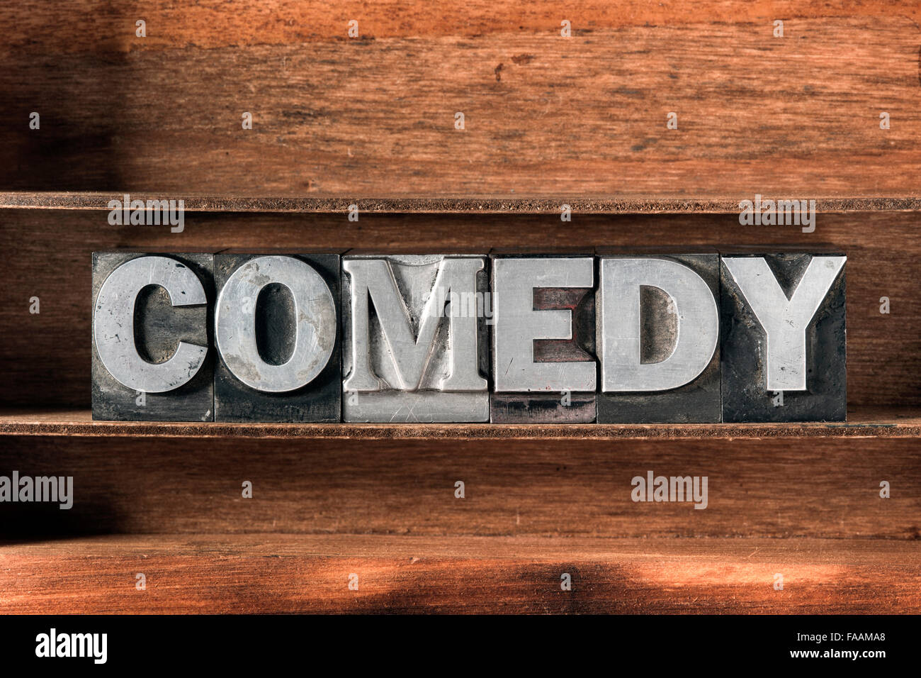 comedy word made from metallic letterpress type on wooden tray - Stock Image
