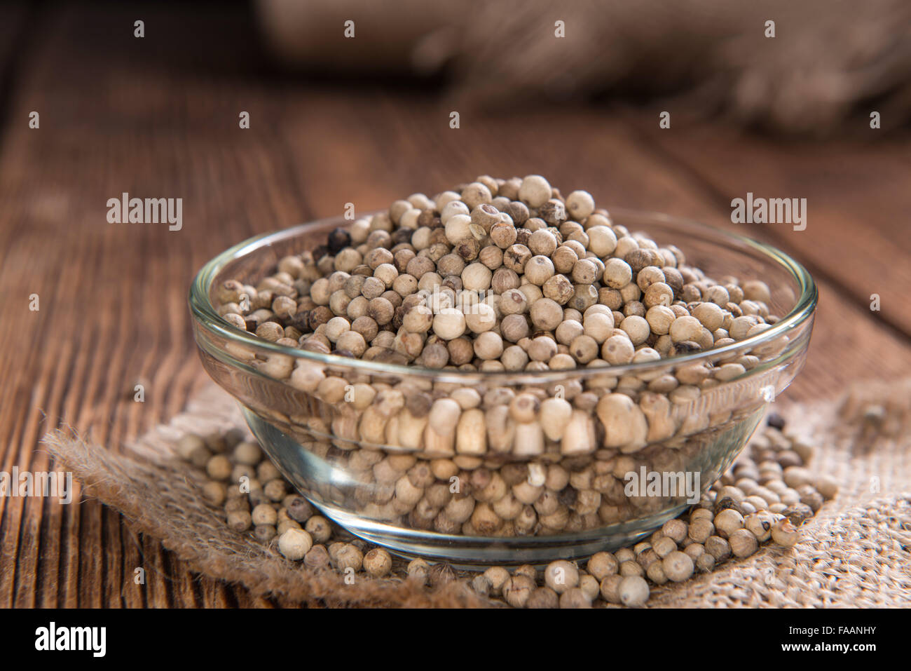 Some white Peppercorns (close-up shot) on wooden background - Stock Image