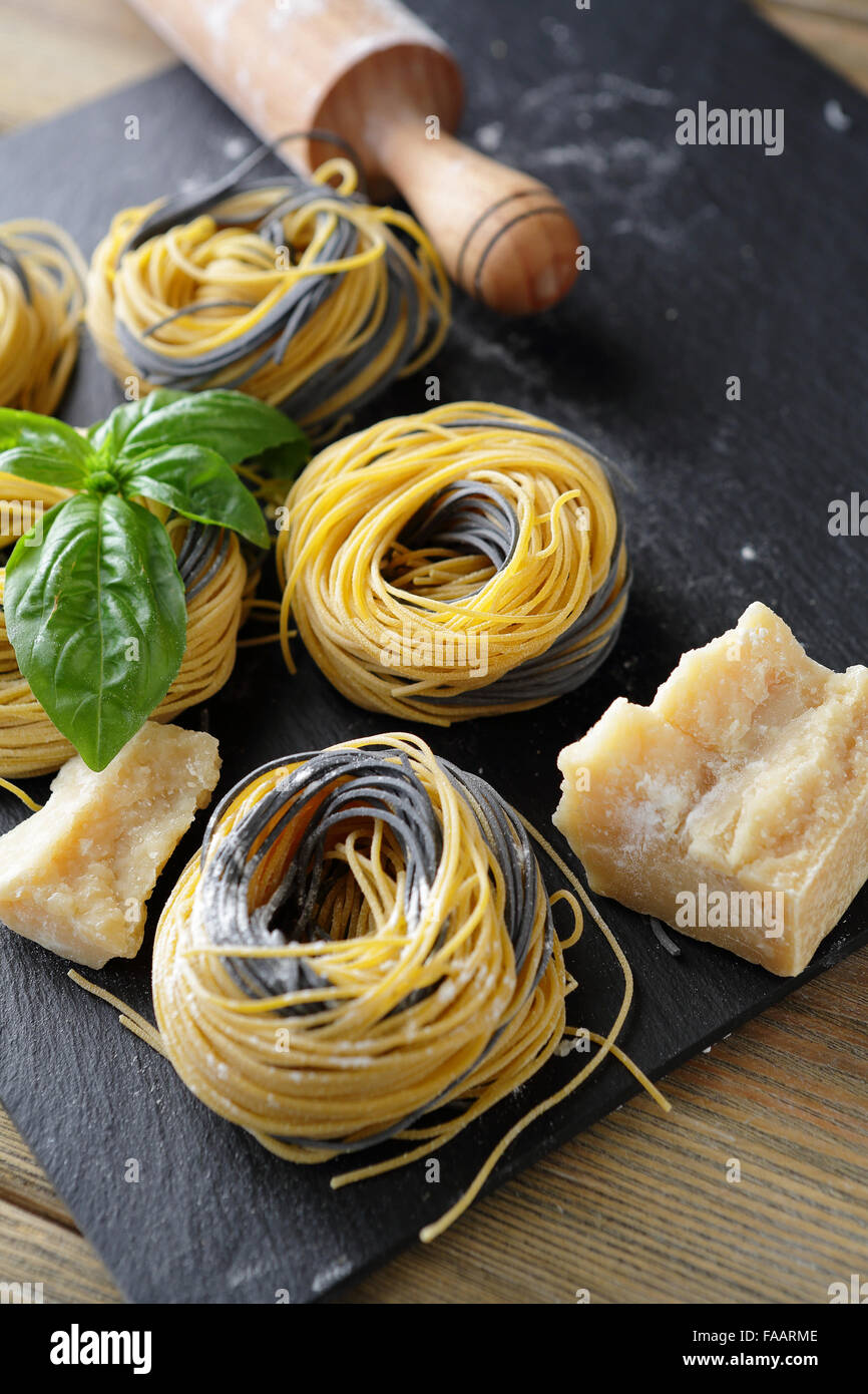raw pasta on slate with cheese, food closeup - Stock Image