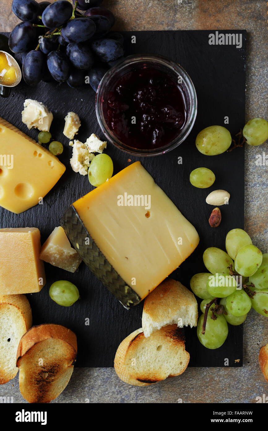 cheese with ripe grapes, food top view - Stock Image