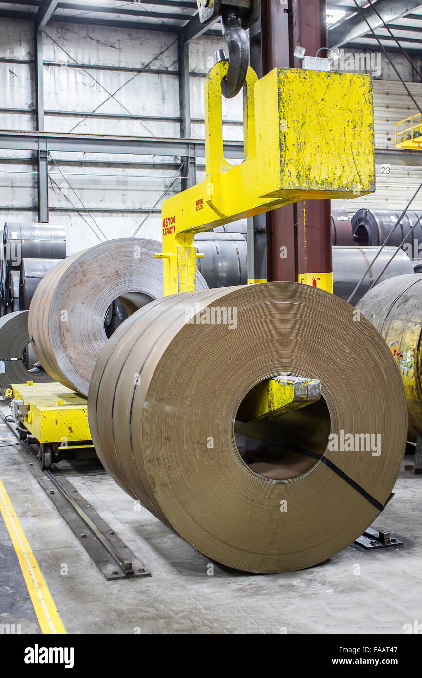 48' wide Steel coil on forty five ton crane claw about to be lifted - Stock Image