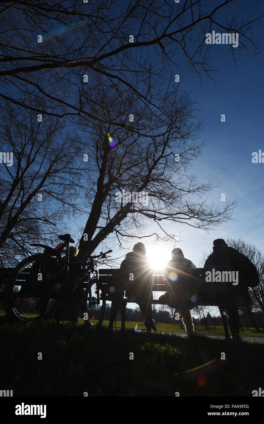 Munich, Germany. 25th Dec, 2015. People sit on a bench in the 'Englische Garten' park in Munich, Germany, - Stock Image