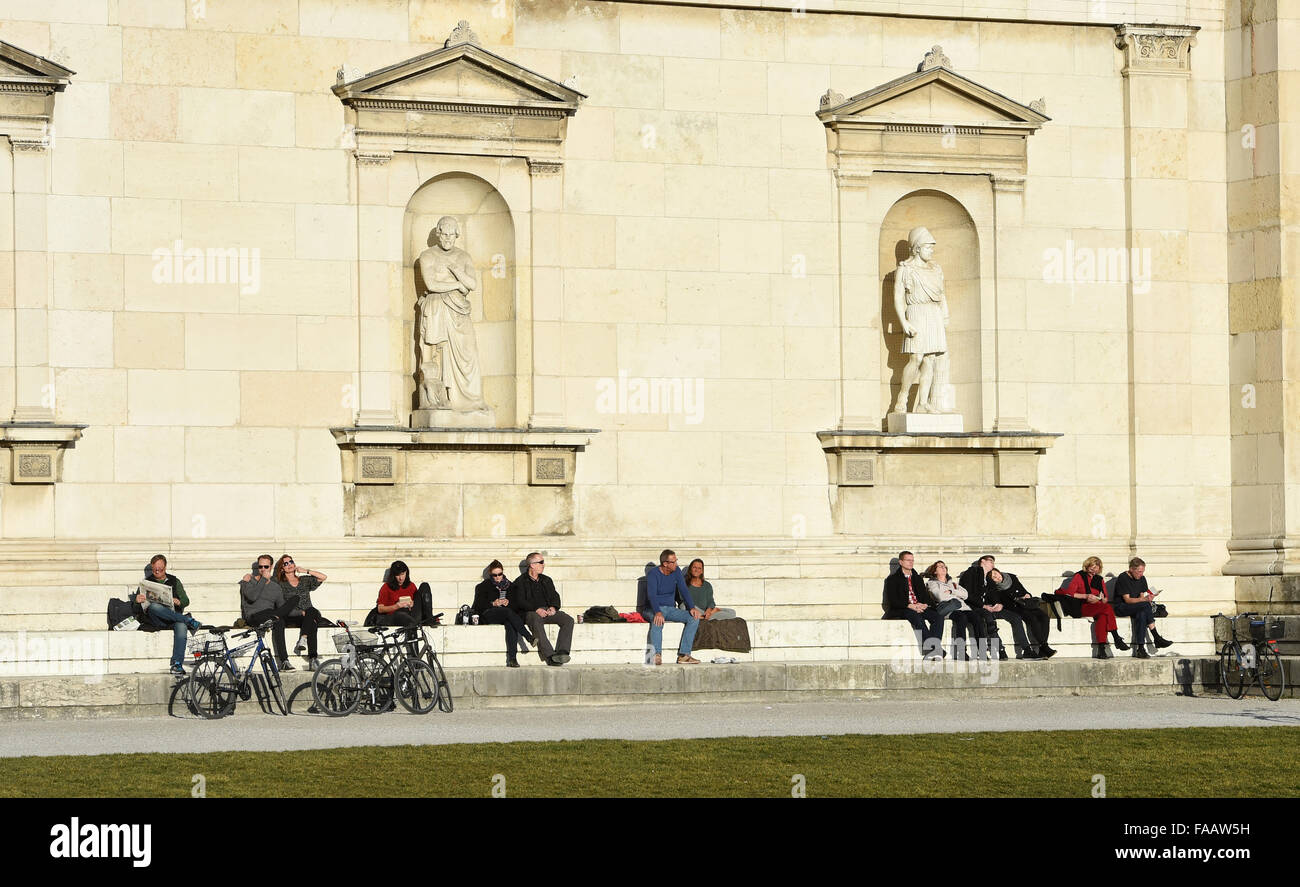 Munich, Germany. 25th Dec, 2015. People sit on a stone ledge as they enjoy the warm sun in front of the 'Glyptothek' - Stock Image