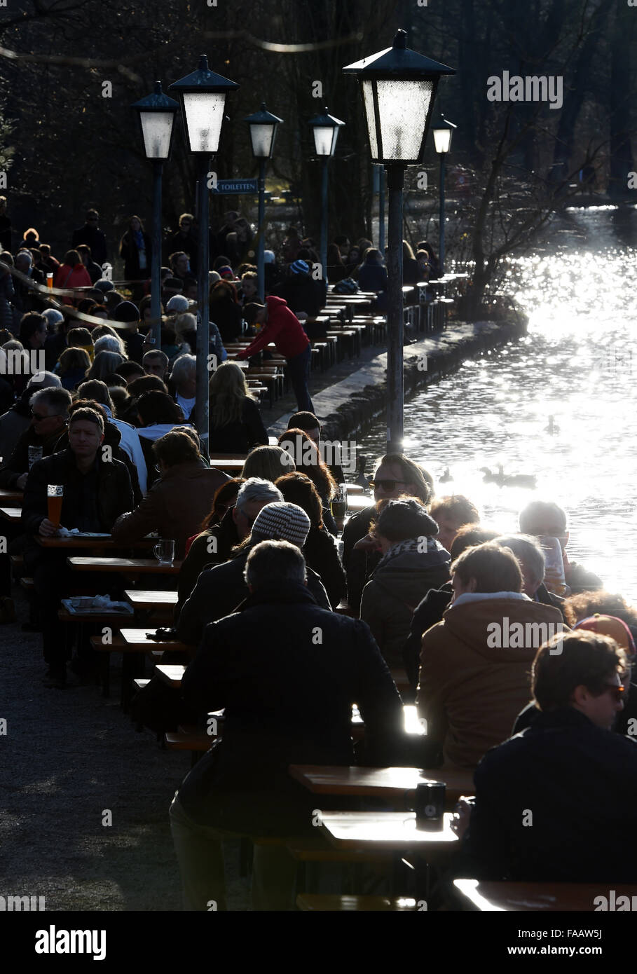 Munich, Germany. 25th Dec, 2015. People sit in the beer garden in the 'Englische Garten' park in Munich, - Stock Image