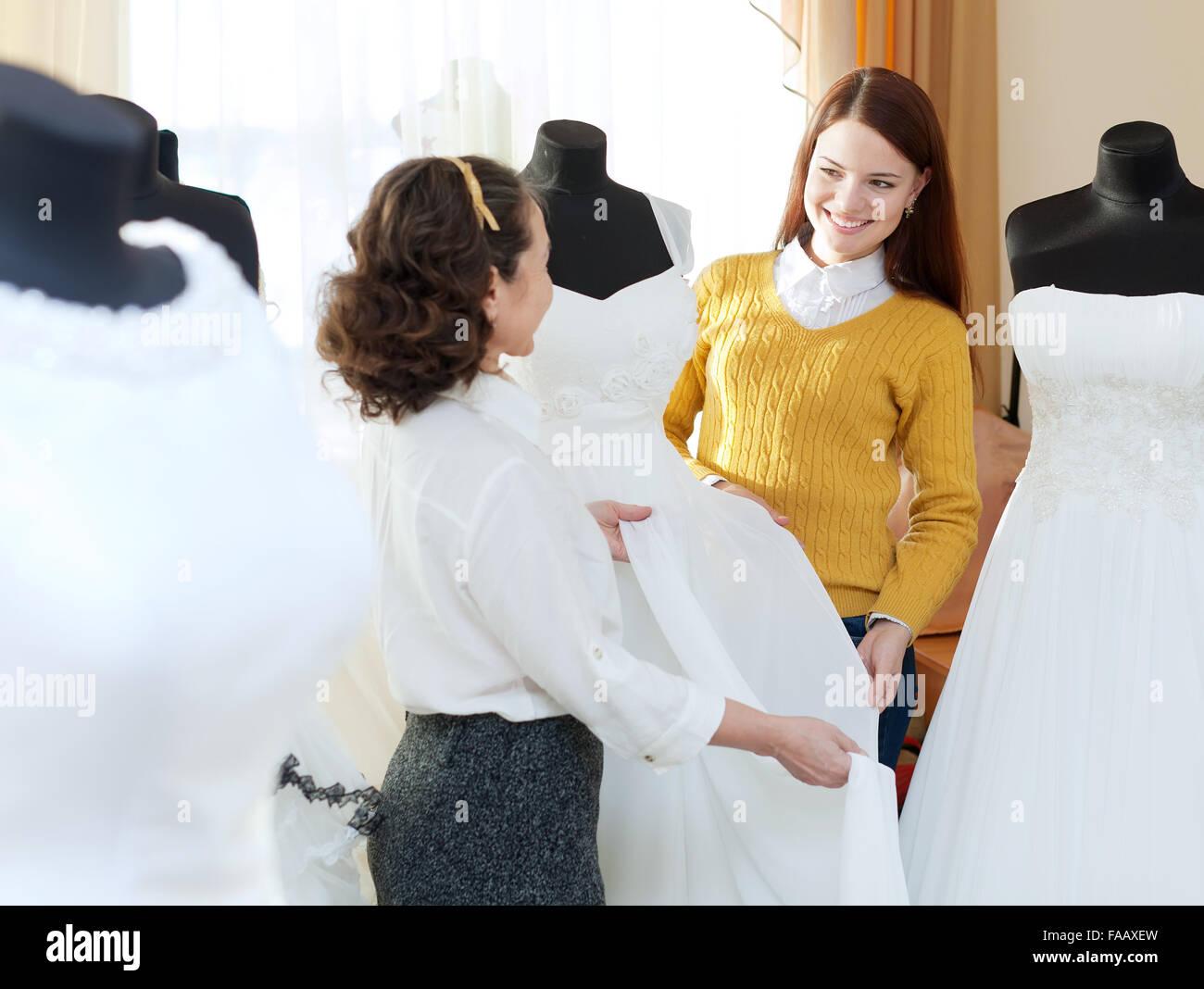 pretty bride chooses bridal dress at wedding store. Shop consultant ...