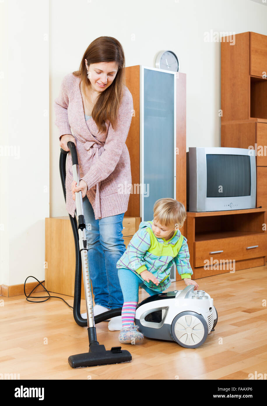 Smiling Girl With Baby Cleaning Living Room With Vacuum Cleaner Stock Photo - Alamy