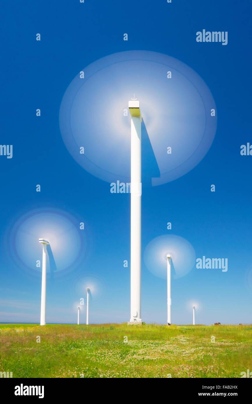 Landscape with moving wind turbine (wind farm) on the blue sky background, Pomerania, Poland - Stock Image