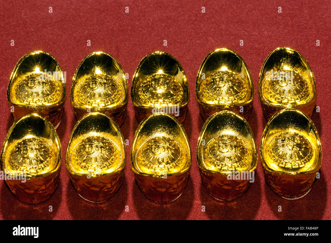 Small artificial Chinese auspicious gold ingots in studio setting - Stock Image