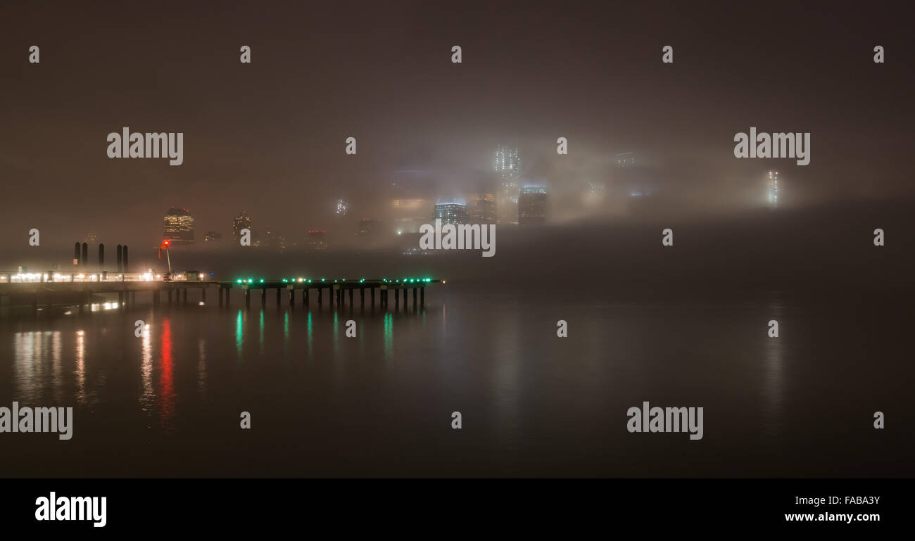 NYC weather - The skyscrapers of Lower Manhattan are enveloped in fog  with lights reflected in the Hudson River. - Stock Image