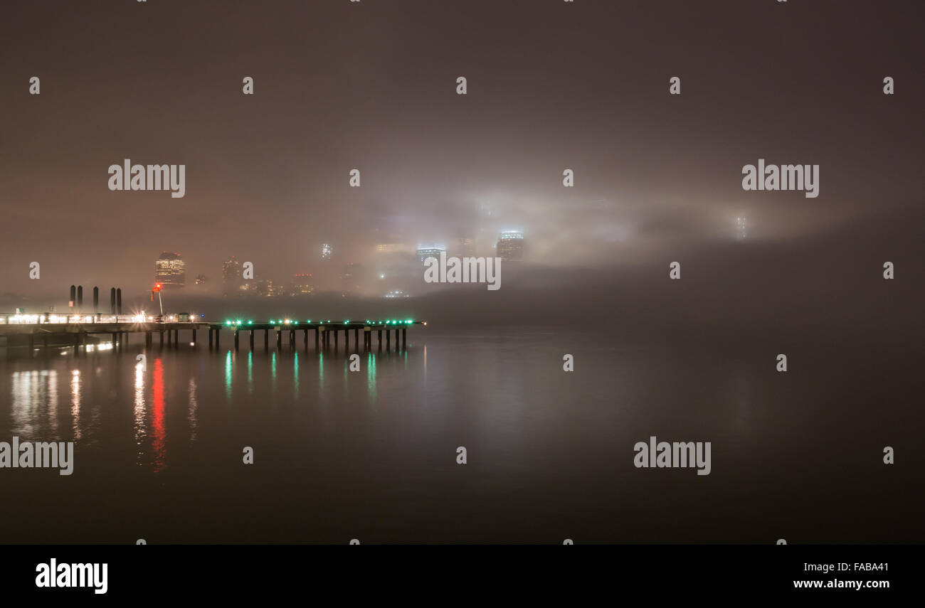 NYC weather - The skyscrapers of Lower Manhattan are enveloped in fog, with lights reflected in the Hudson River. - Stock Image