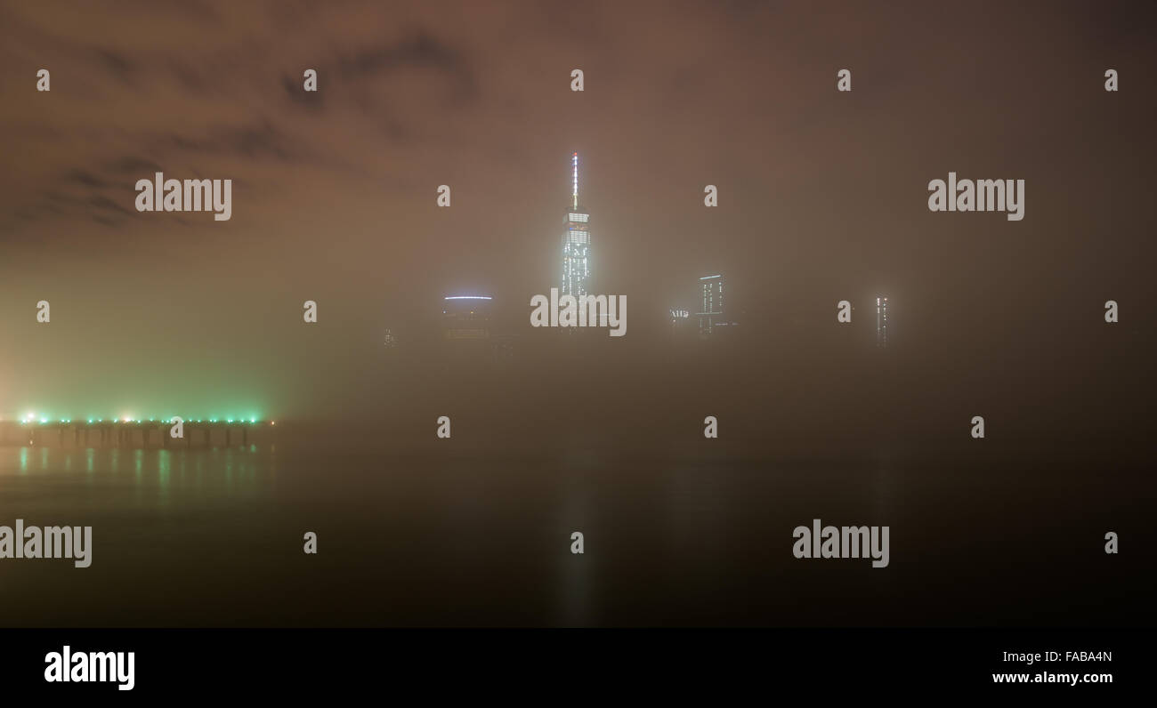 NYC weather - The skyscrapers of Lower Manhattan are enveloped in fog , with lights reflected in the Hudson River. - Stock Image