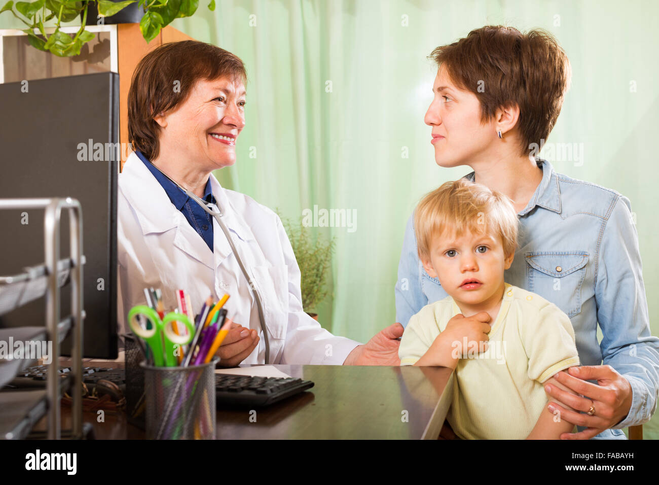 mother with baby talking with friendly pediatrician doctor at clinic - Stock Image