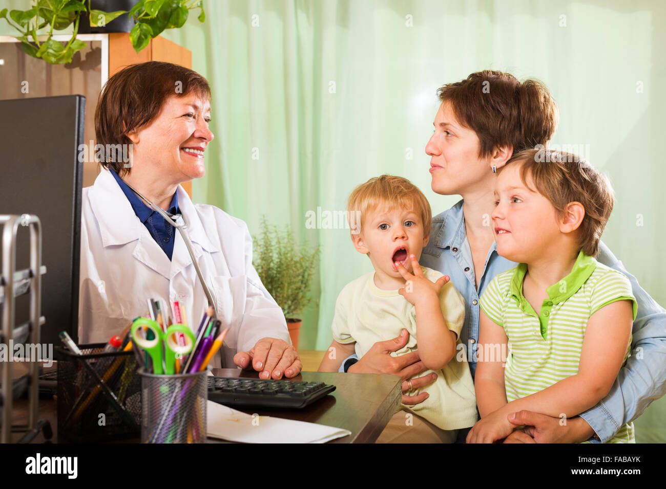 Young  mother of two children  talking with friendly pediatrician doctor at clinic office - Stock Image