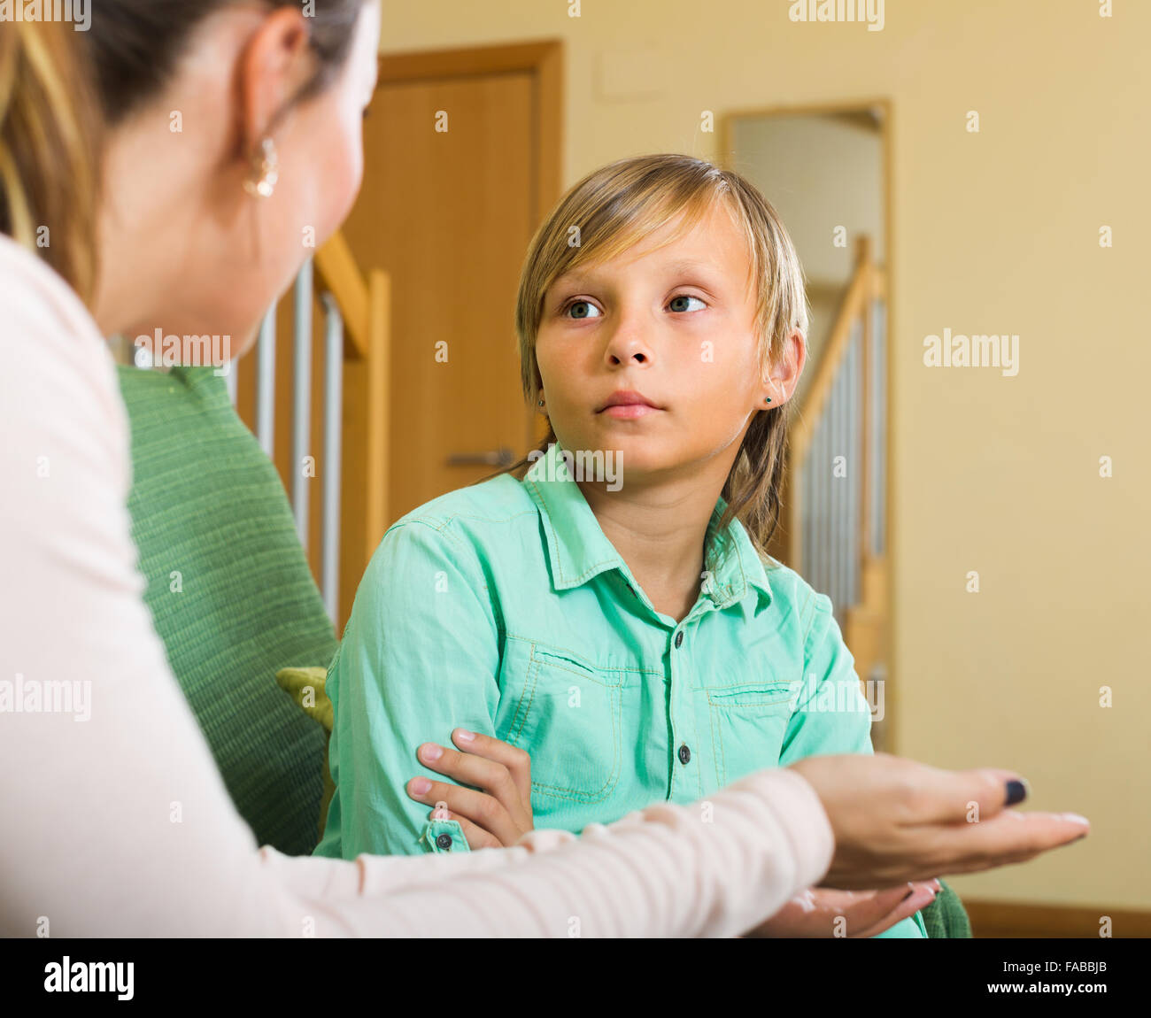 Serious Mother Scolding Naughty Teenage Son In Home Interior Stock Image