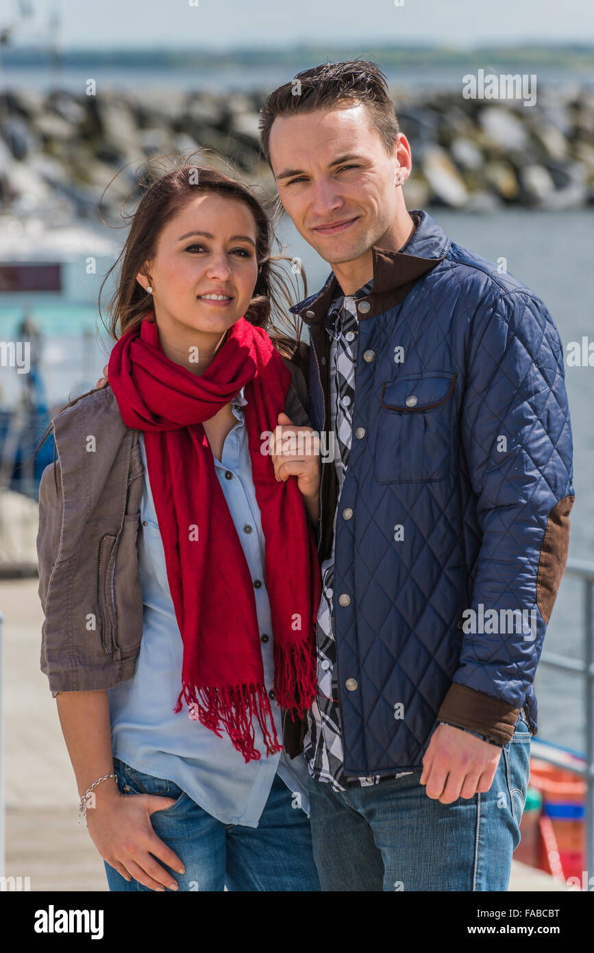Couple 25-30 age standing in a harbor at the Baltic sea - Stock Image
