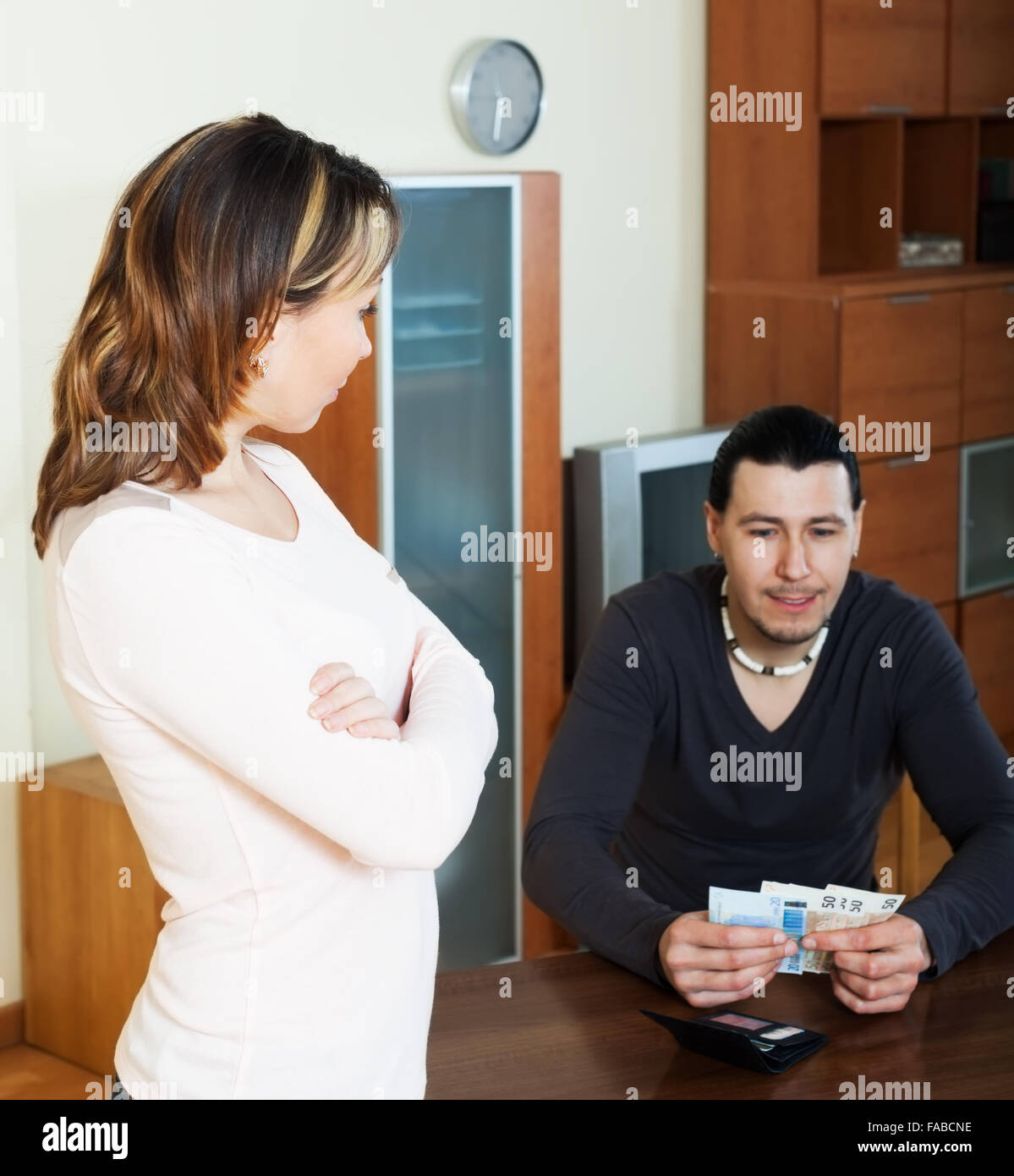 Financial problems in family. Man counting cash, woman watching him in home - Stock Image
