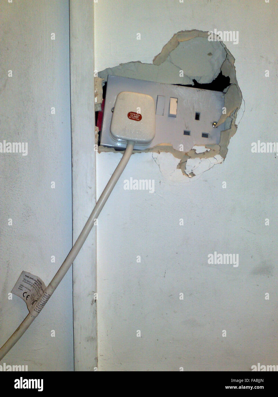 Kicked in electric wall socket - Stock Image