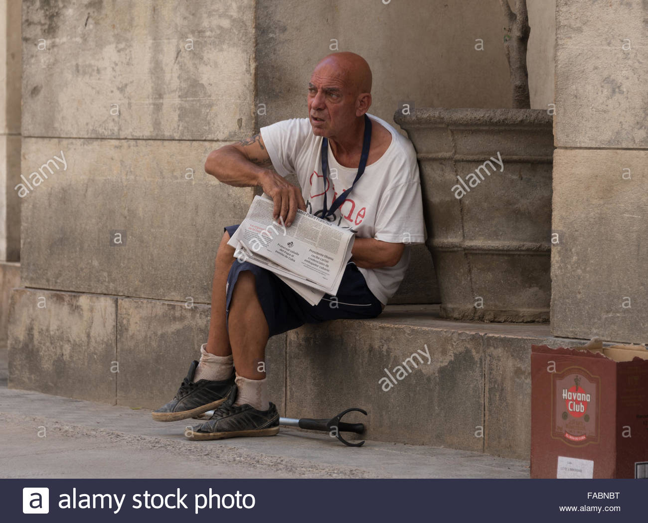 Old needy man selling newspapers in Old Havana,Cuba. Newspapers are often bought by tourists as souvenirs of one - Stock Image