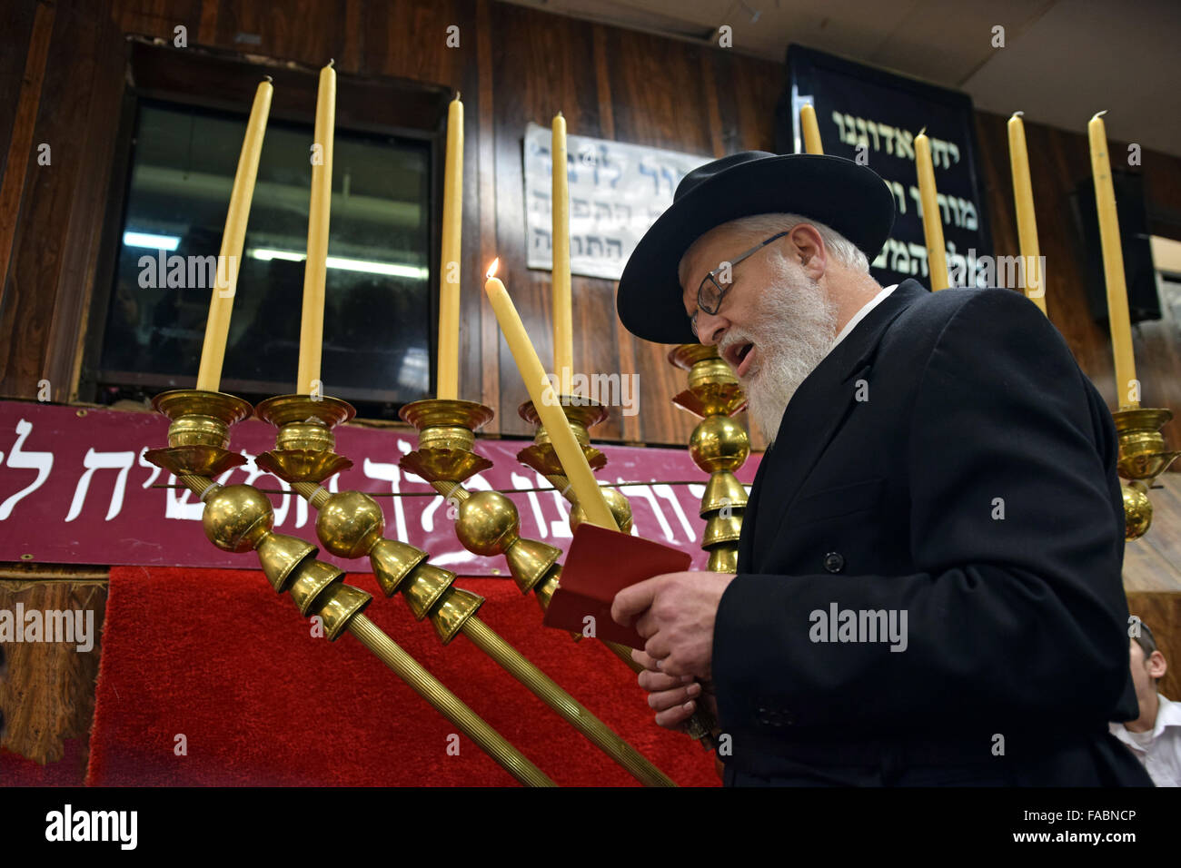An orthodox Jewish rabbi reciting the blessings before lighting the candles on a giant Chanukkah menorah. In Brooklyn, - Stock Image