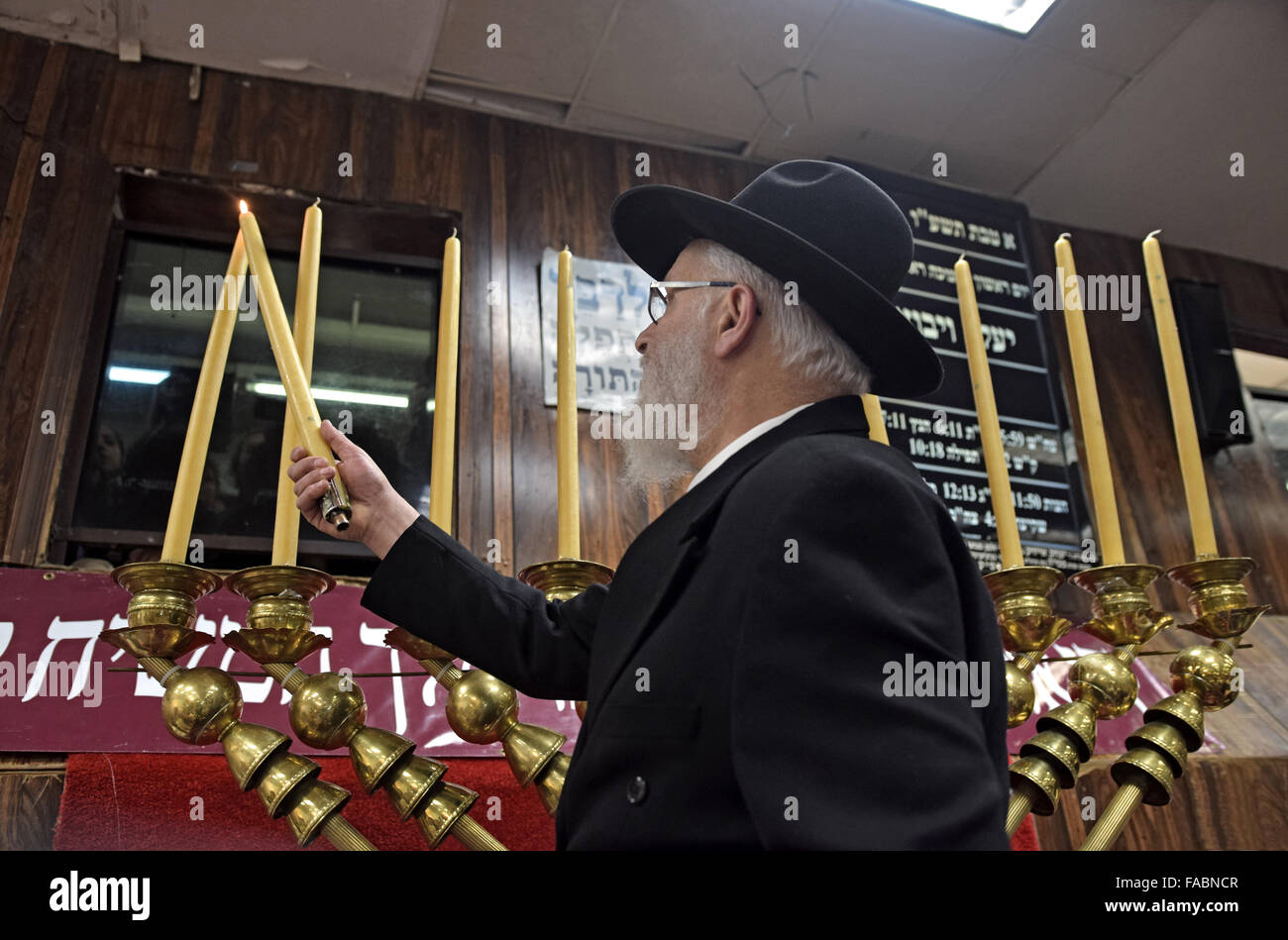 An orthodox Jewish rabbi lighting the candles on a giant Chanukkah menorah. In Brooklyn, New York - Stock Image