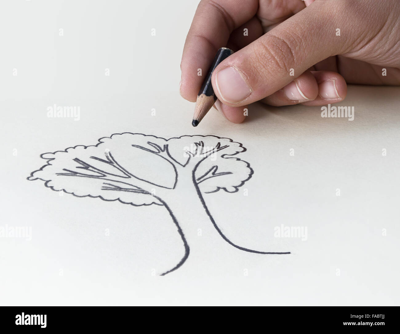 A child drawing a tree with a very short pencil stub expressing he concept of the