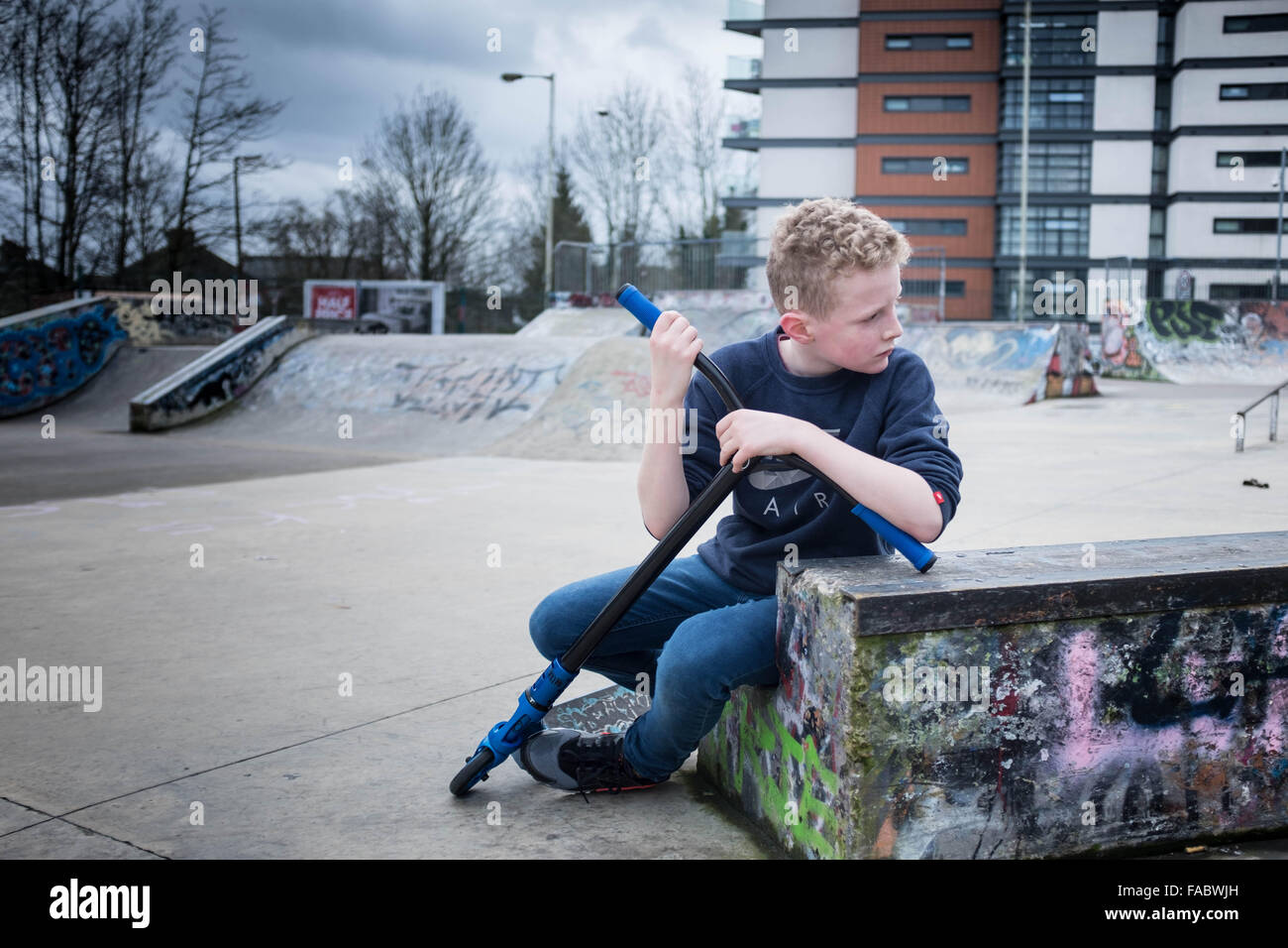 Young, blonde 12 year old boy, alone looking pensive in an urban skate park environment - Stock Image