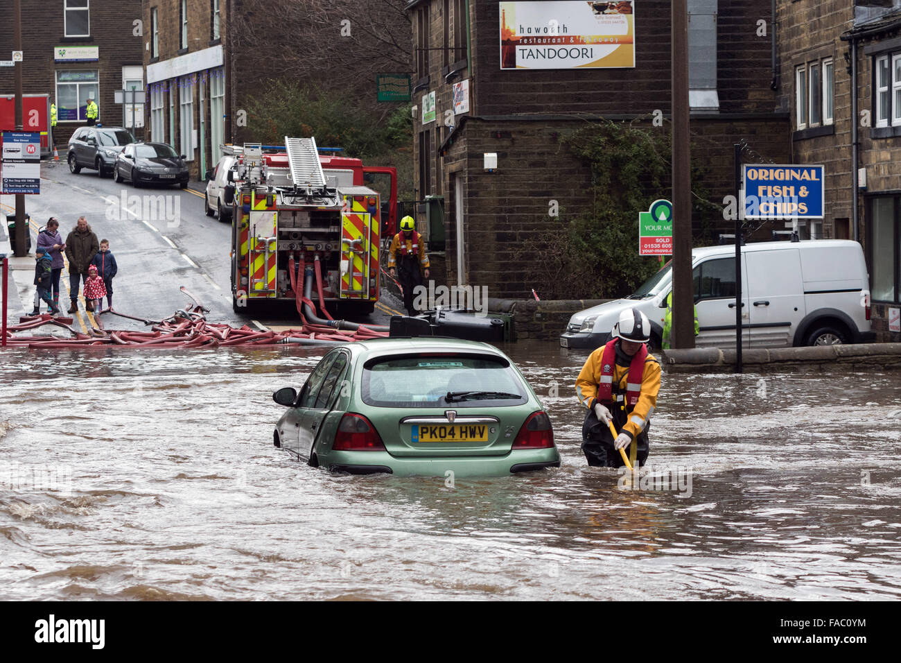 Haworth, UK. 26 December 2105. A firefighter makes his way through floods at Haworth, West Yorkshire following heavy Stock Photo