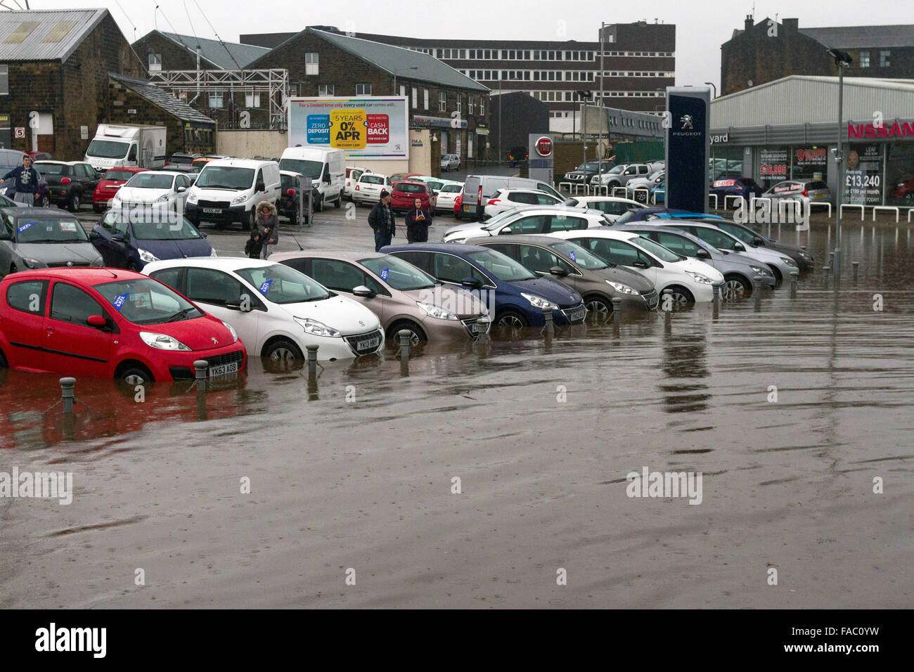 Keighley, UK. 26 December 2105. Cars at a dealership stand partly submerged during floods in Keighley, West Yorkshire Stock Photo
