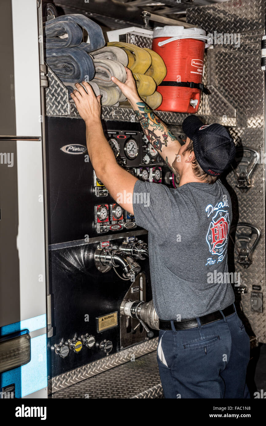 A back view of a fire fighter with large arm tattoo wearing a gray department t-shirt checking the hoses on his - Stock Image