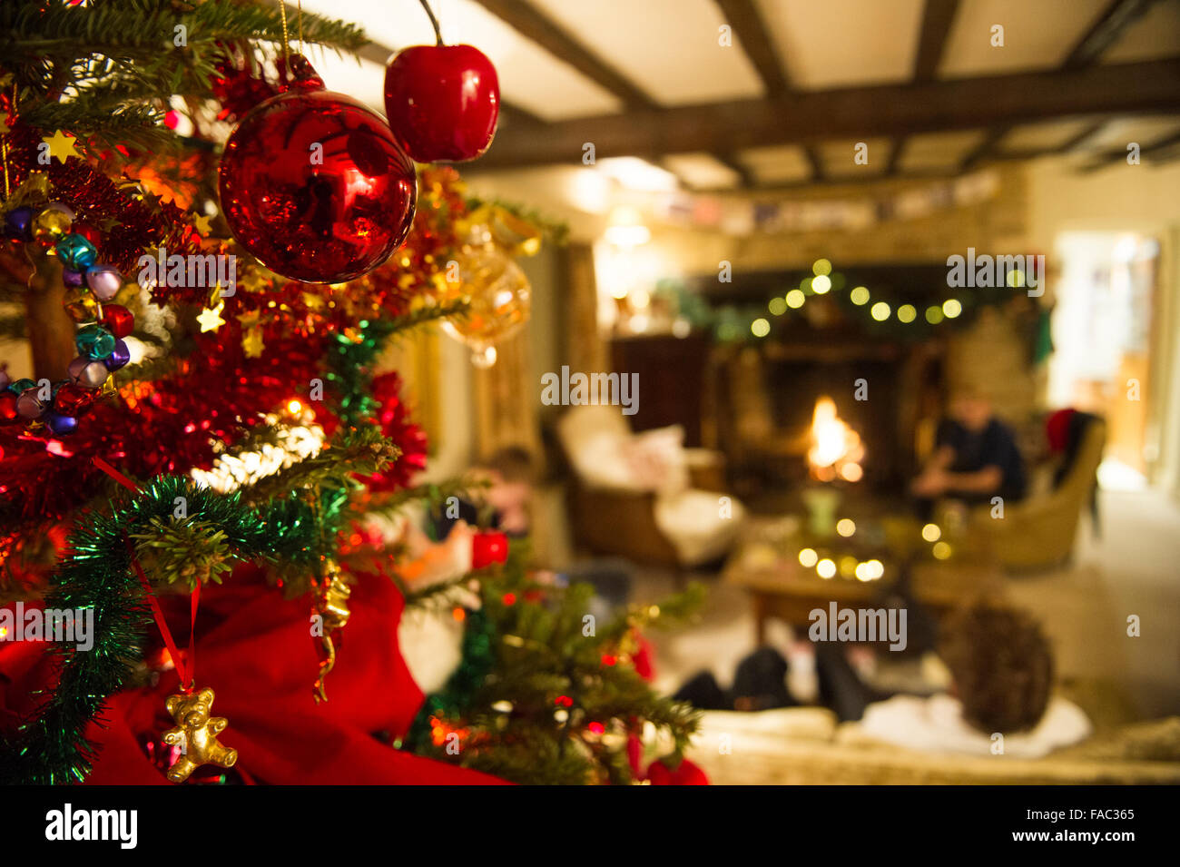 A Warm Family Scene On Christmas Day With Tree In Country Cottage An Open Fire And Decorations