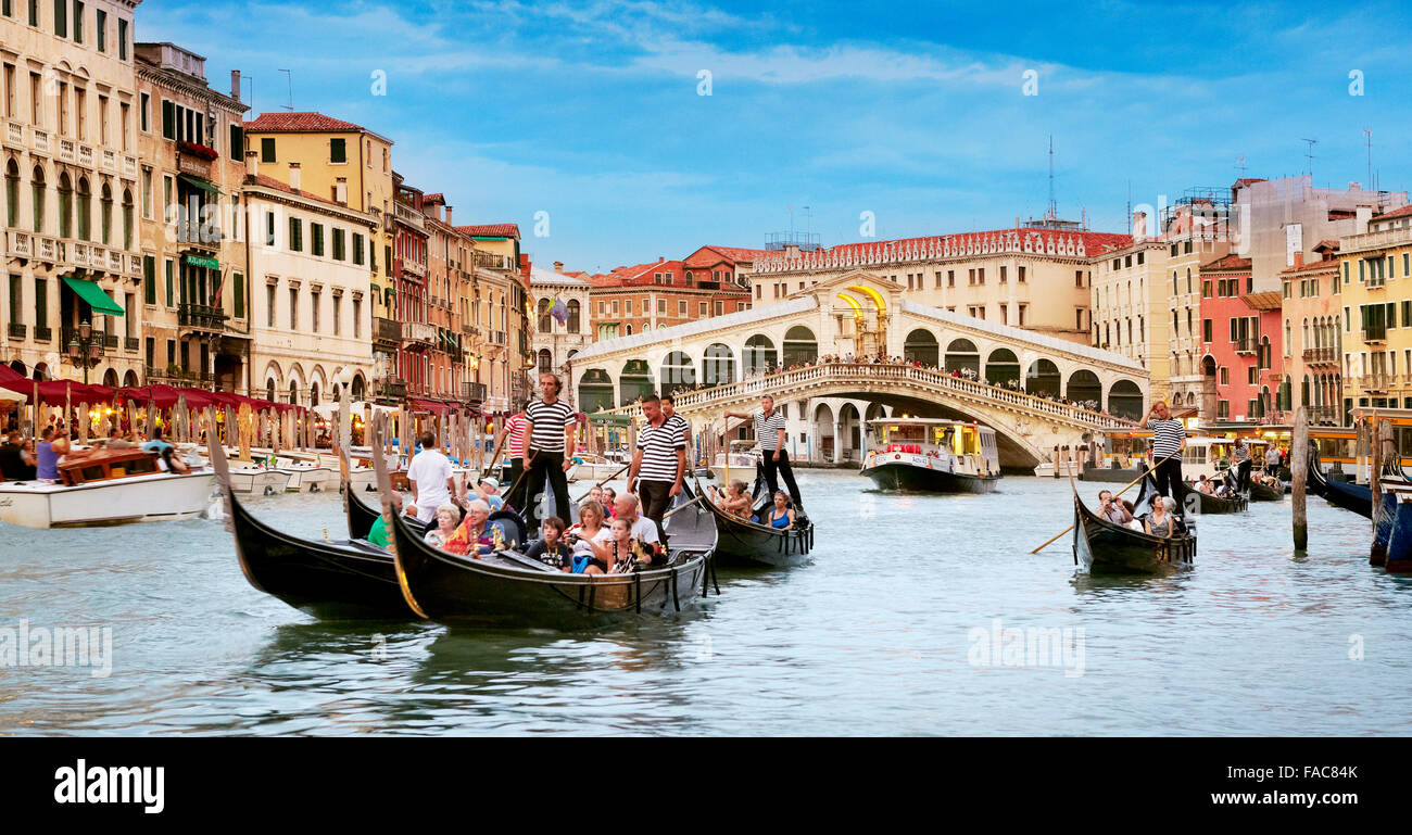 Tourists in gondola exploring Grand Canal, Rialto Bridge in the background, Venice, Italy - Stock Image