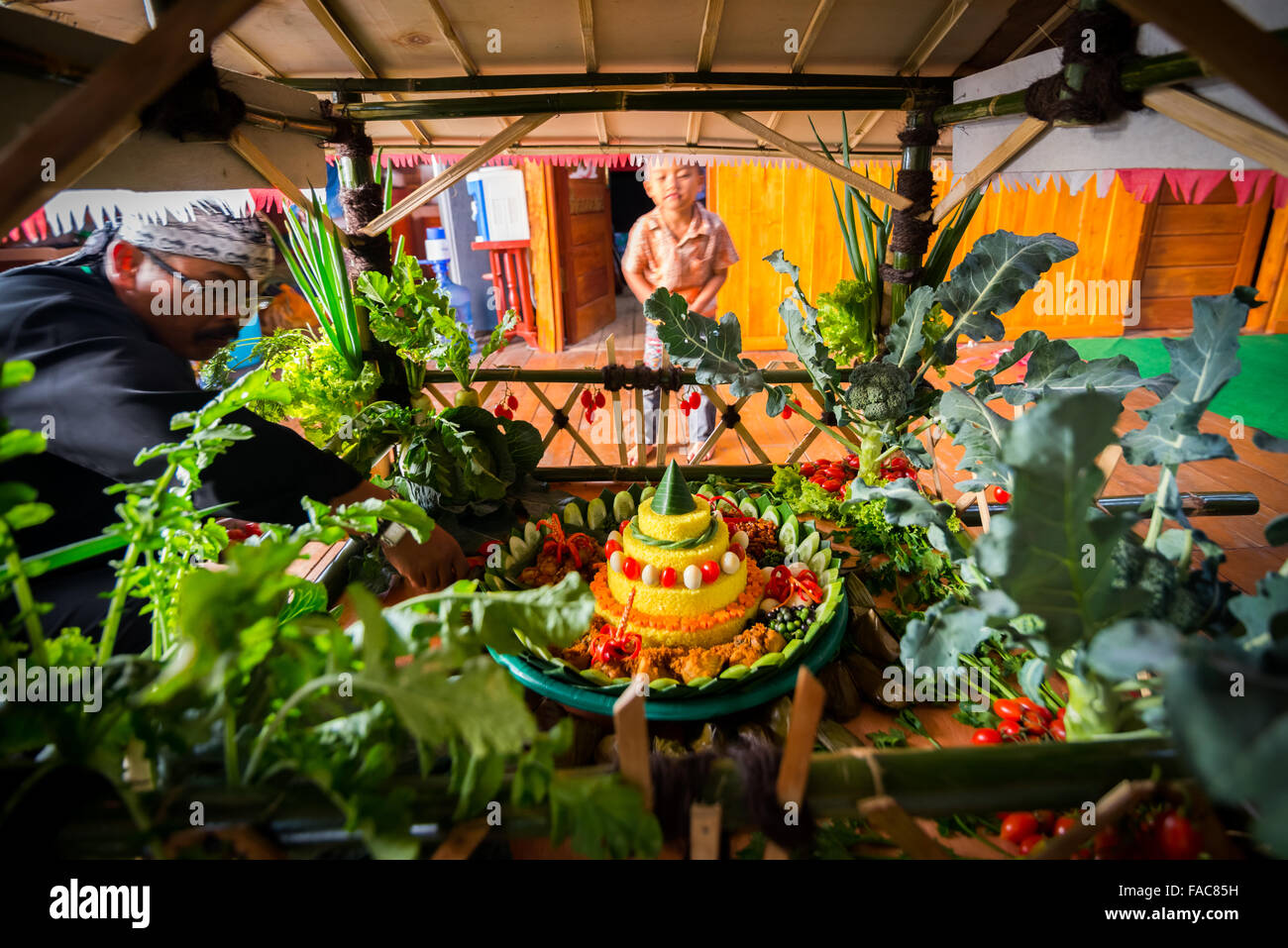 Sundanese man preparing traditional offering set consists of rice, vegetables, and fruits. - Stock Image