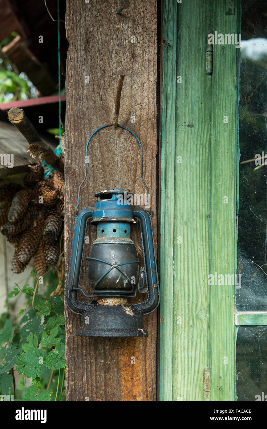 old oil lamp hanging outside a house - Stock Image