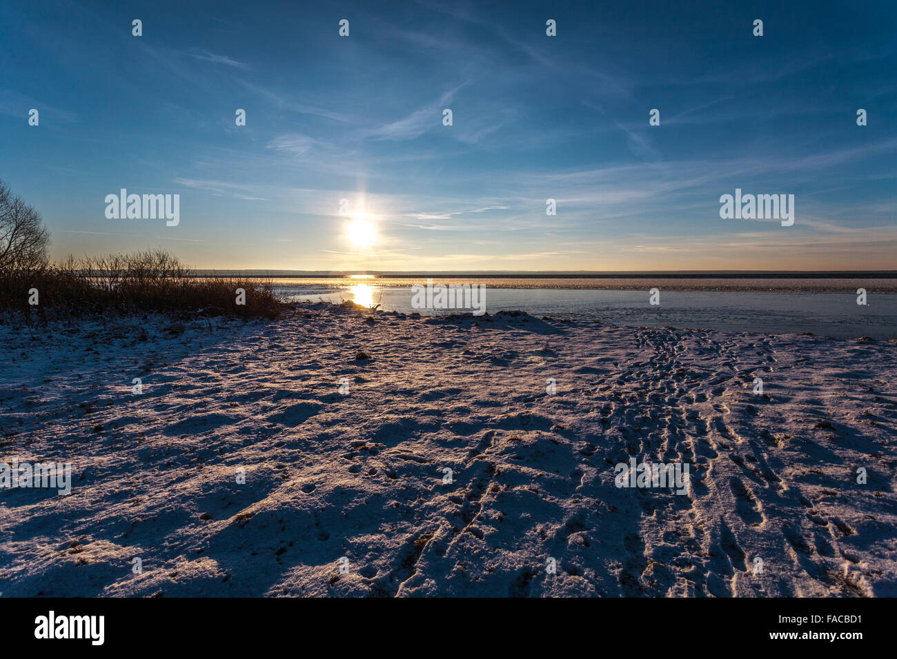 The sun concerns the horizon on the winter coast, being reflected from snow, water and ice. - Stock Image