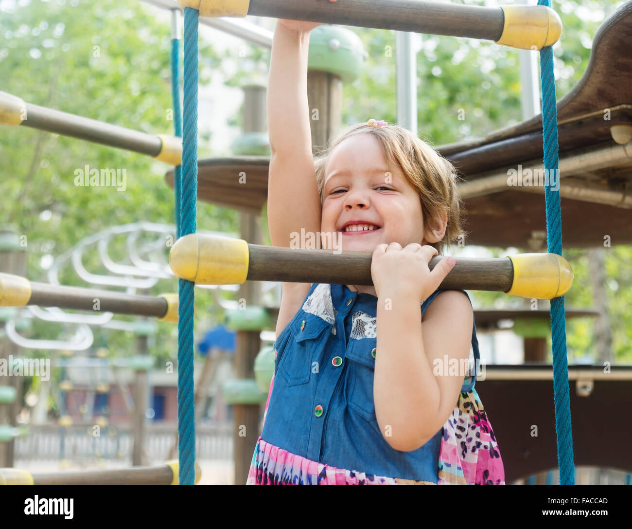 Smiling girl developing dexterity at playground - Stock Image
