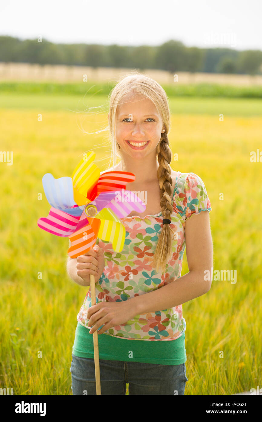 Girl with windmill in a cornfield - Stock Image