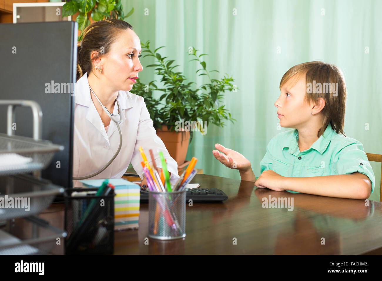 Female doctor at the table listening to complaints boy patient - Stock Image