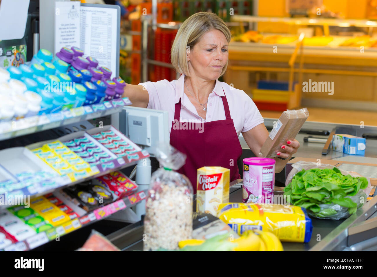 Stressed cashier at the supermarket - Stock Image