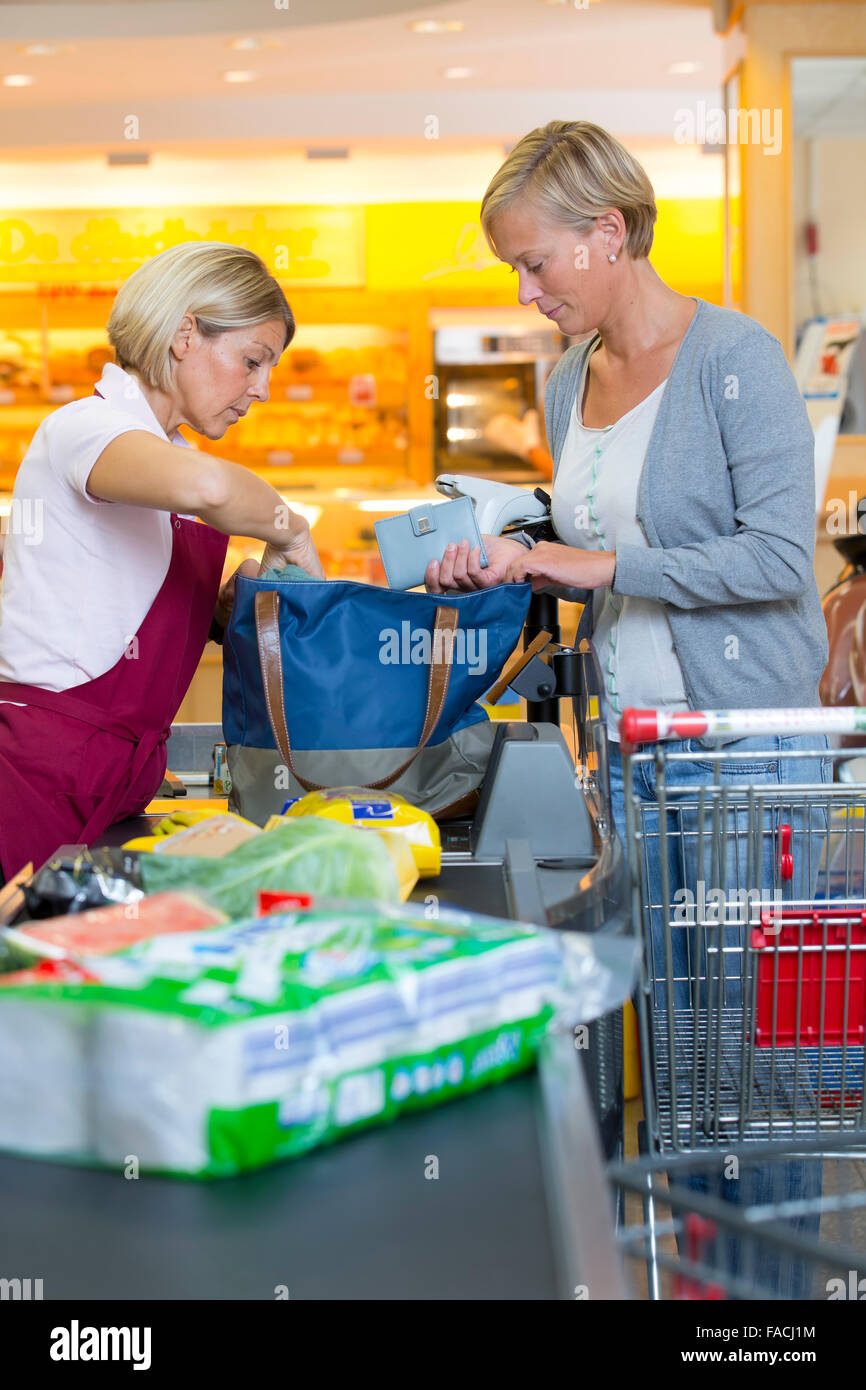 Cashier rummages through the pocket of a customer - Stock Image