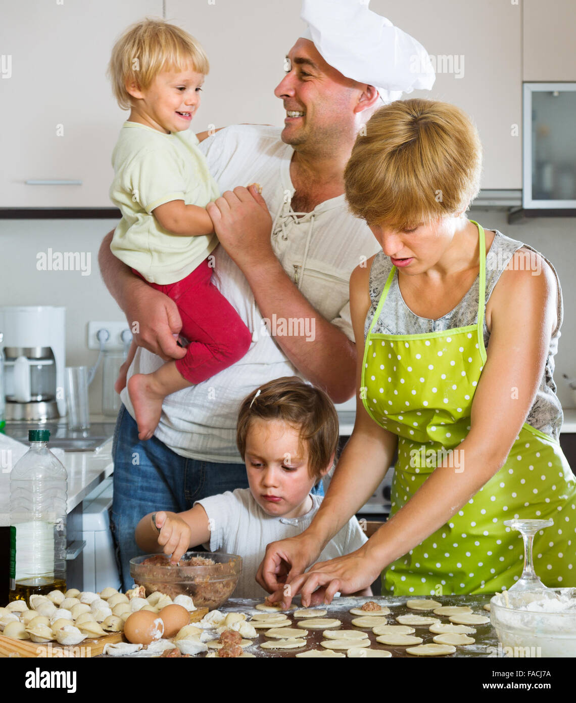 Happy parents with children cooking meat dumplings at home