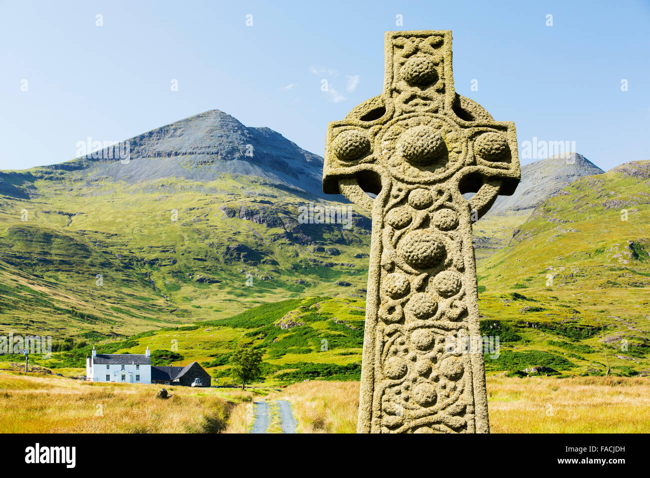 An isolated house beneath Ben More on the Isle of Mull, Scotland, UK and a stone cross. - Stock Image