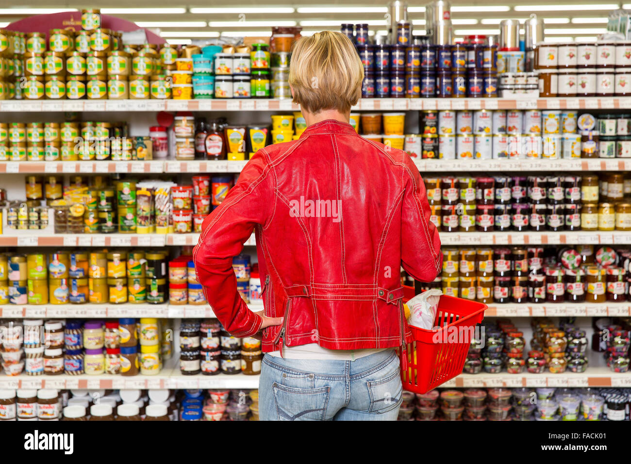 Woman in supermarket shelf before with many products - Stock Image