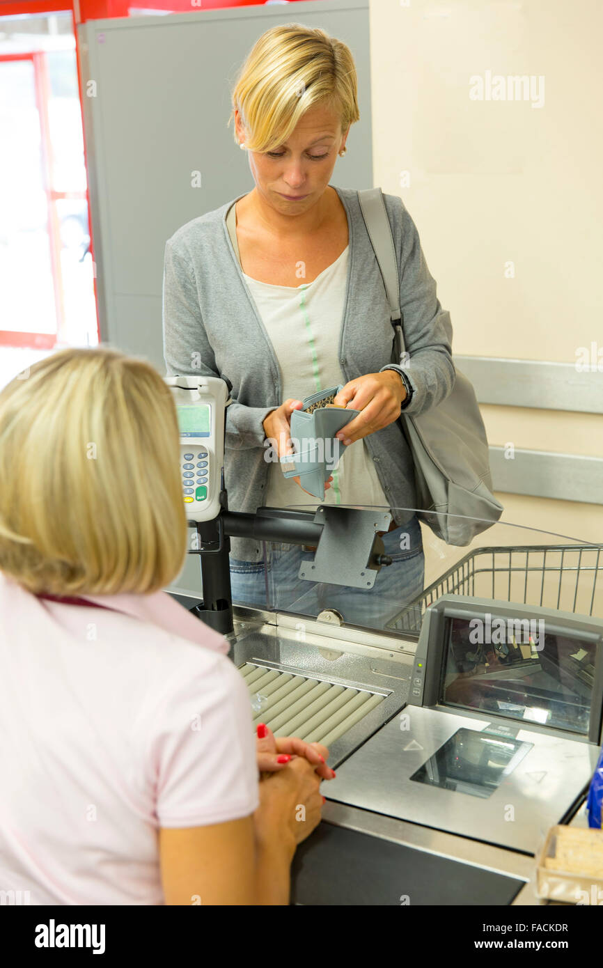 Customer at the checkout at the grocery store looking shocked into her wallet - Stock Image