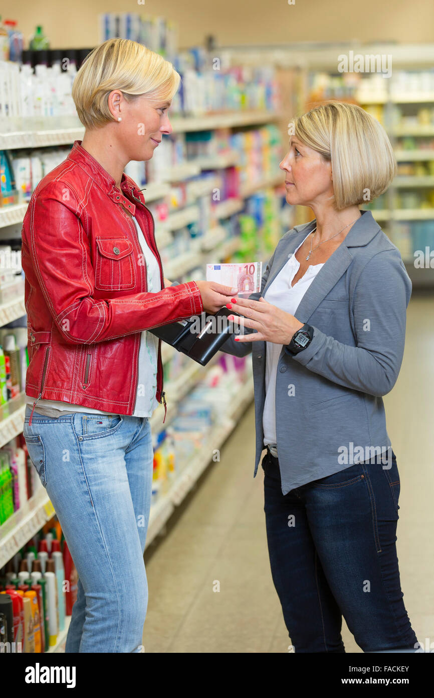 Woman borrows her friend money at the supermarket - Stock Image