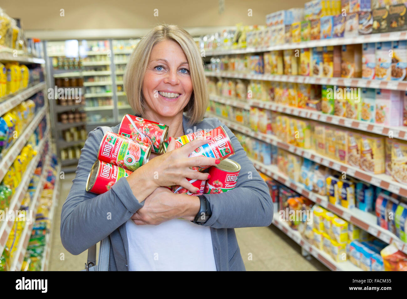 Woman buys many canned in supermarket - Stock Image
