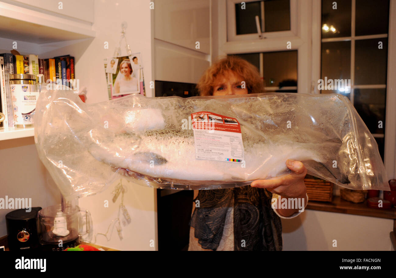Woman holding a whole shop bought Salmon in a bag from Asda Stock Photo