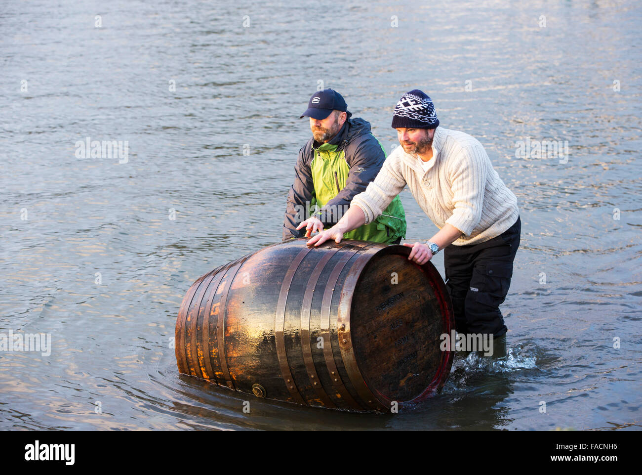 Two men recover a beer barrel washed away into Lake Windermere by the floods in Ambleside in the Lake District on - Stock Image