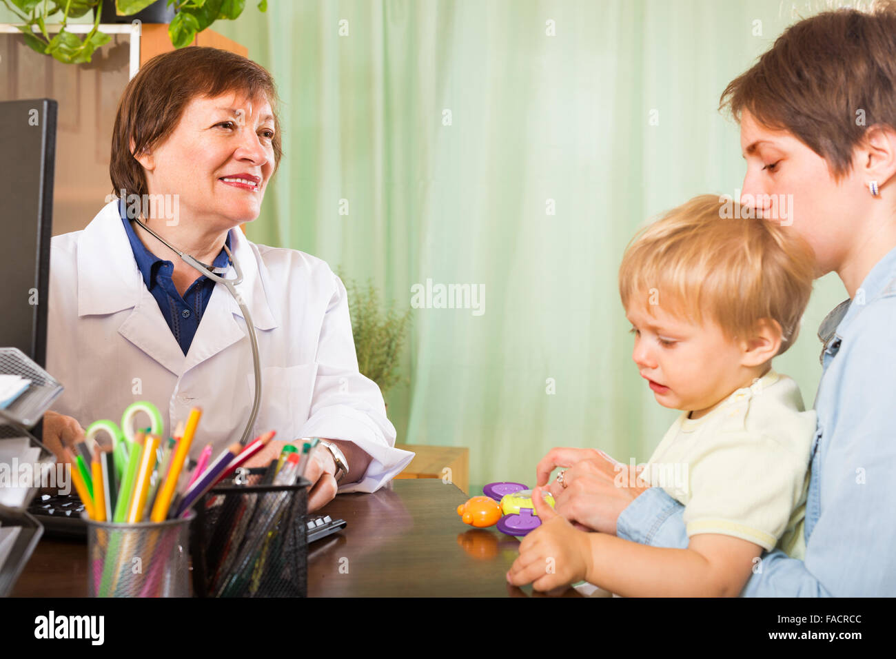 Mother with toddler talking with smiling female pediatrician doctor at clinic - Stock Image